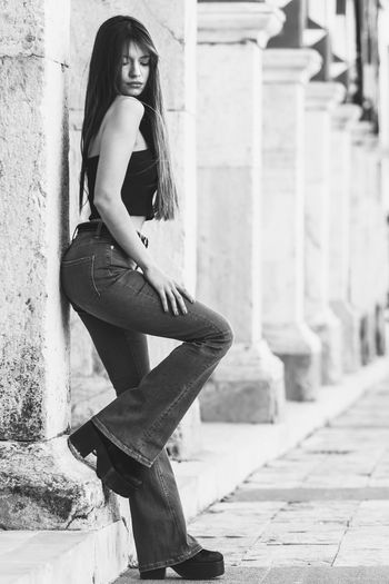 Black and white portrait of beautiful woman on the street Architectural Column Beautiful Woman Black And White Black And White Photography Blackandwhite Building Exterior Built Structure Casual Clothing Contemplation Focus On Foreground Full Length Hair One Person Outdoors Real People Teenager Women Young Adult Young Women