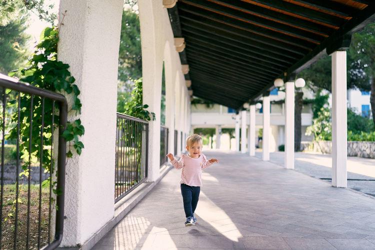 Full length of woman on footpath by bridge