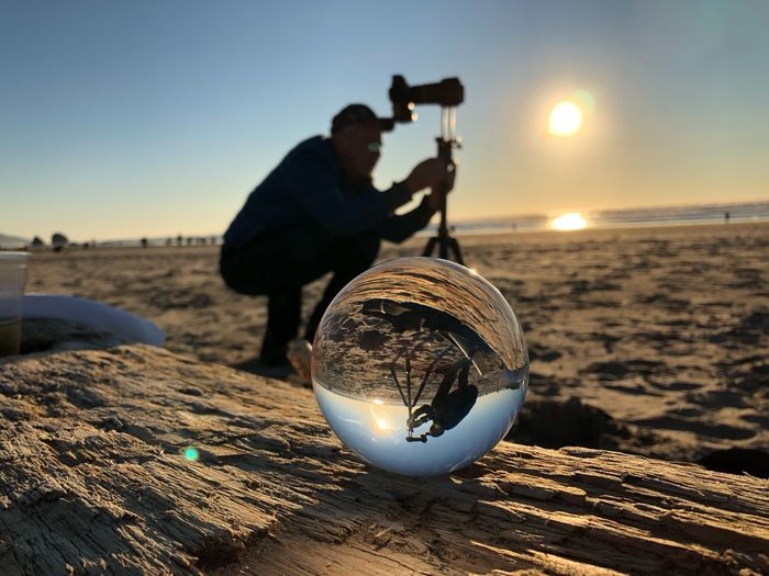 Man holding camera at beach against sky during sunset