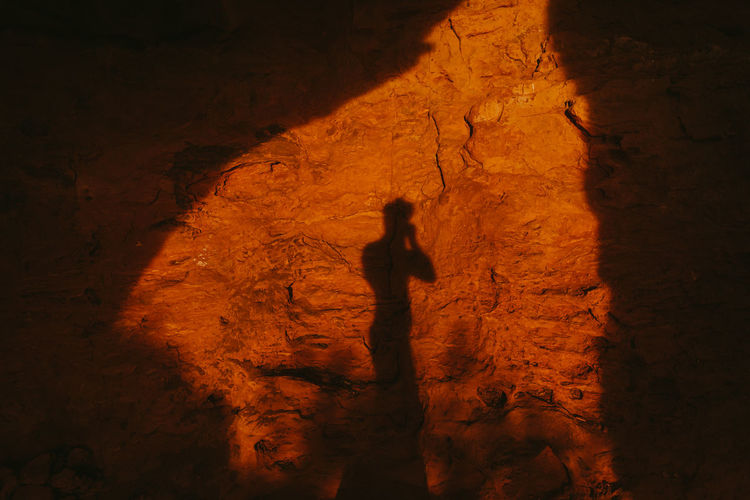 High angle view of silhouette man standing on rock