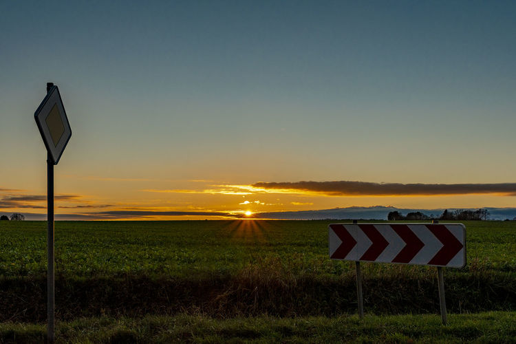 sunset Signs Horizon Over Land Farmland Grassland Niedersachsen Sky Sunset Tranquil Scene Tranquility Land Nature Beauty In Nature Grass Scenics - Nature No People Field Environment Landscape Sunlight Sun Plant Flag Idyllic Orange Color Outdoors