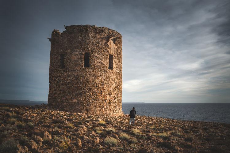 Girl at cala domestica coastal tower
