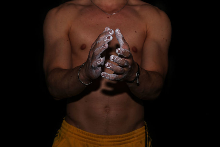 Midsection of shirtless man hands covered with talcum powder against black background