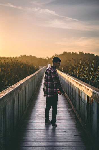 Man standing on footpath by bridge against sky during sunset