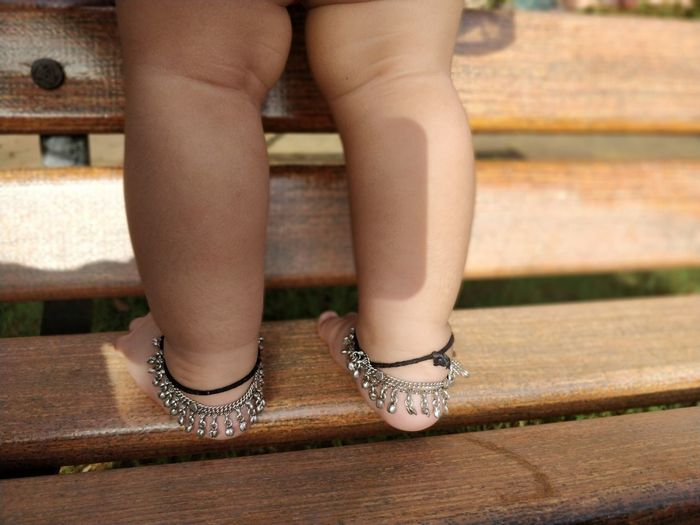 Low section of baby girl wearing anklets standing on bench