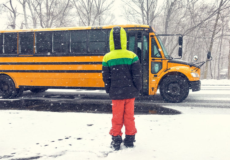 Winter Snow Mode Of Transportation Transportation Cold Temperature Land Vehicle Real People Warm Clothing City Clothing One Person Yellow Bare Tree Day Tree Street Car Road Motor Vehicle Snowing Outdoors School Bus
