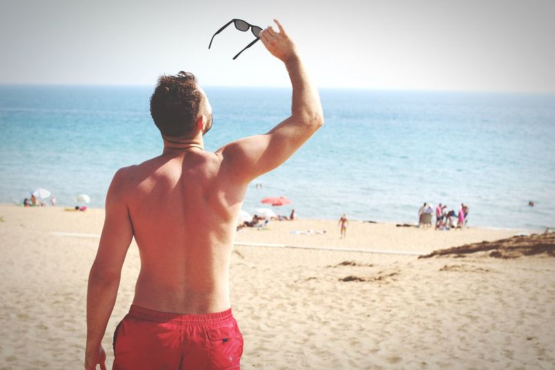 Rear view of shirtless mid adult man holding sunglasses while standing at beach against clear sky