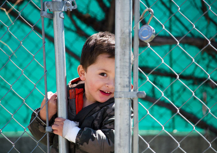 Portrait of cute boy looking through chainlink fence