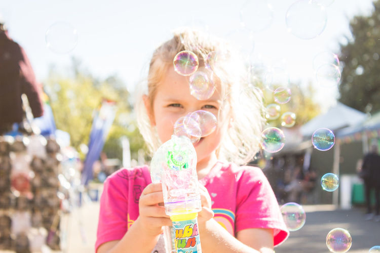 Portrait of girl holding bubbles