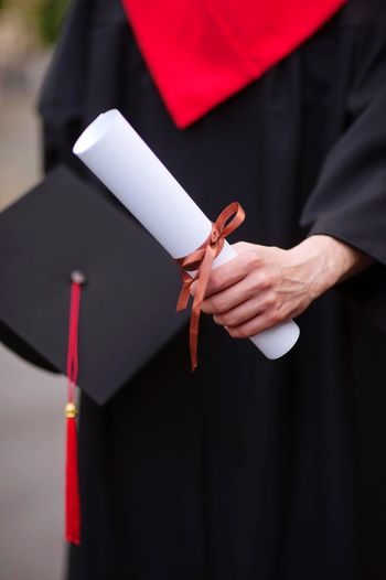 Midsection Of Male University Student Holding Degree