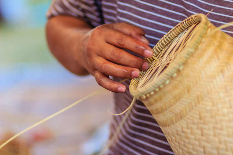 Midsection of man making wicker decoration