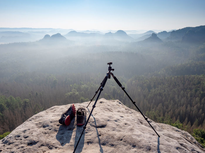 Modern professional travel tripod and black red sneakers on mountain summit. hiking and takes photos