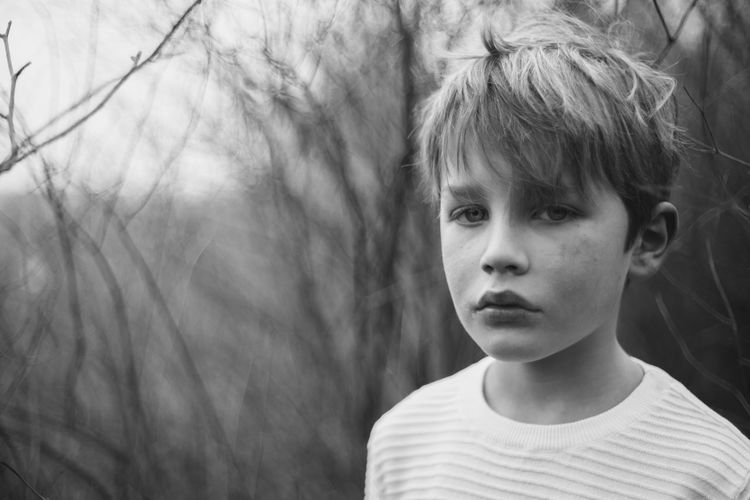 Close-Up Portrait Of Boy In Forest