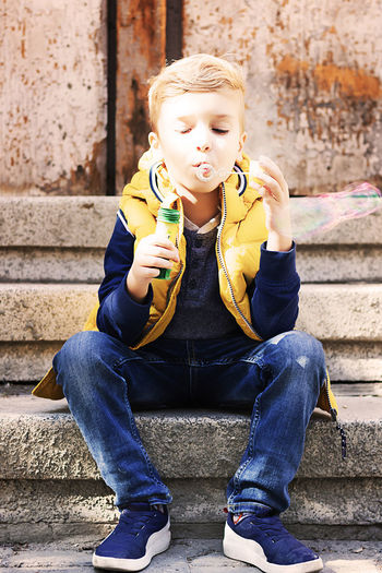 Portrait of boy sitting on staircase