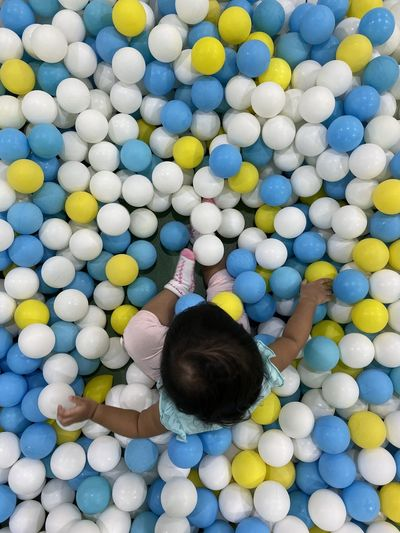 Directly above shot of baby girl sitting at ball pool