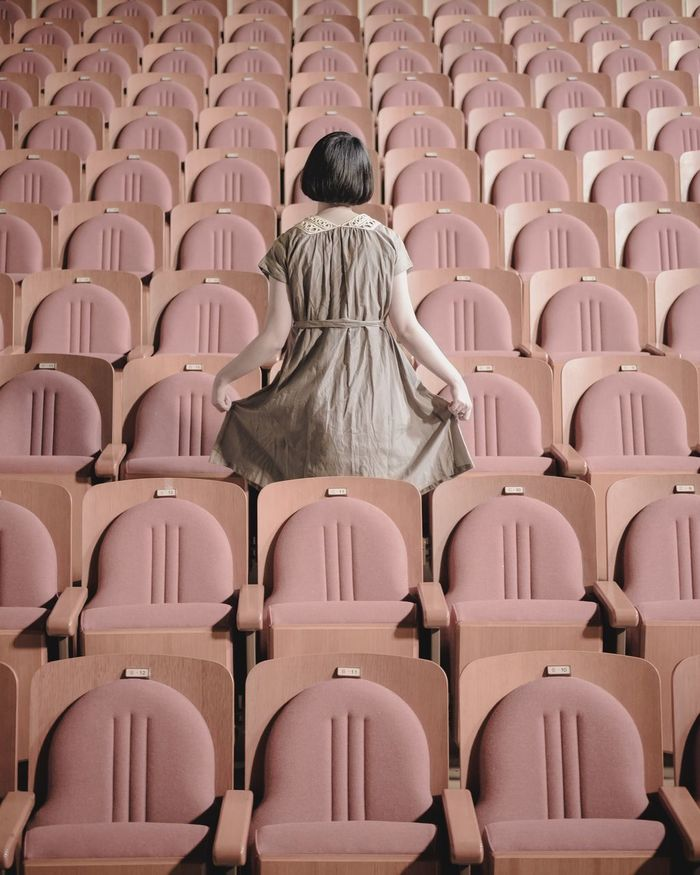 Rear view of woman standing in theater