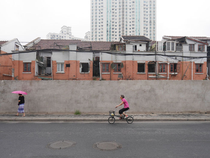 Mobility In Mega Cities Shanghai Streets Architecture Bicycle Building Exterior Built Structure City City Life Cycling Day Land Vehicle Mode Of Transport Outdoors People Riding Road Street Streetphotography Transportation Colour Your Horizn Stories From The City