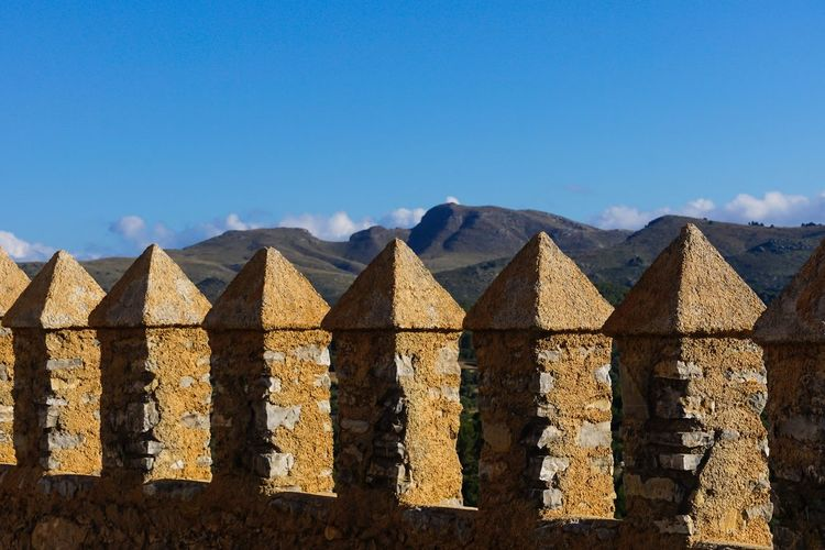 Fortified wall at burg castle by mountains against sky
