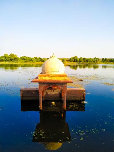 Cross on lake against clear blue sky