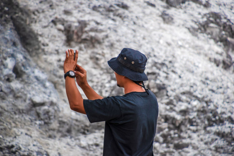 An asian man taking a picture with his cellphone on a rock, rear view
