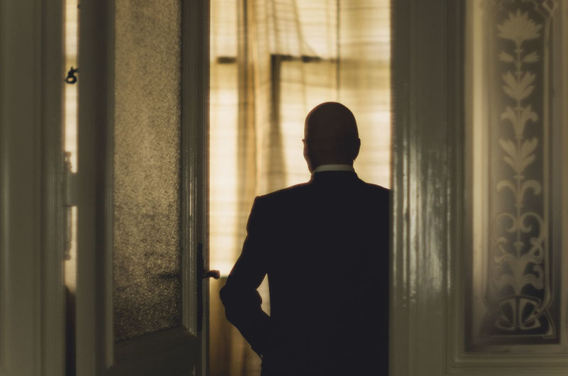 Rear View Of Businessman In Suit Standing By Door
