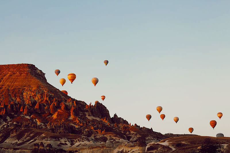 Hot air balloons flying over rocks against sky