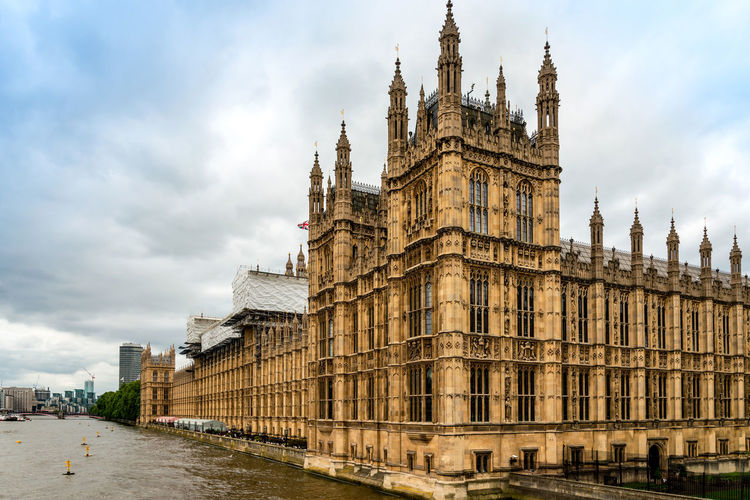Low angle view of big ben by thames river against cloudy sky