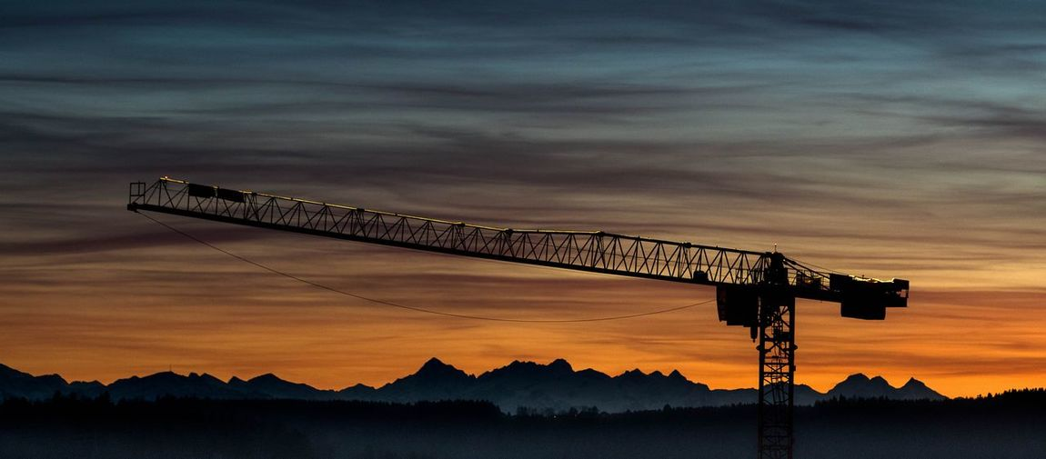 Silhouette crane against sky during sunset