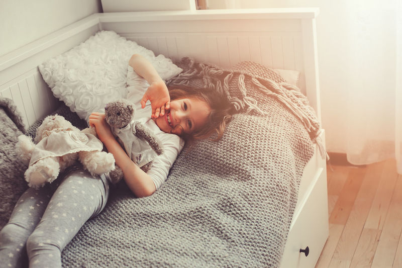 happy kid girl walking up in early morning in her room, playing with teddy bears Real People Indoors  Childhood Home Interior One Person Lifestyles Child Bed Playing Morning Waking Up Teddy Bear Toy Girls Kids Being Kids Kids Playing Authentic Moments Nursery Preschooler Funny Candid