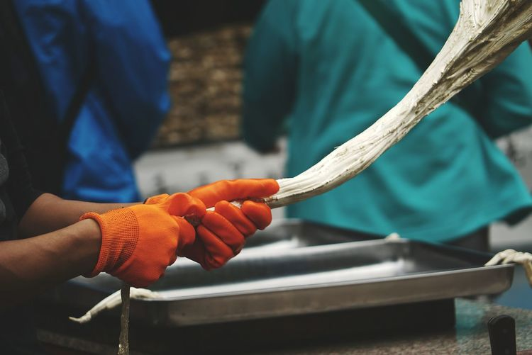 Cropped image of worker pulling taffy at factory