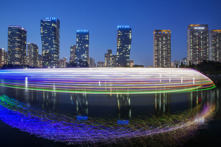 Multi colored light trails on illuminated buildings in city at night