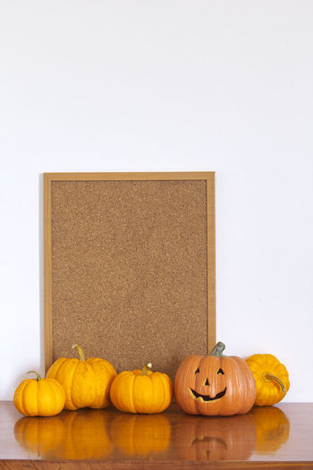 Jack o lantern with pumpkins and bulletin board against white wall