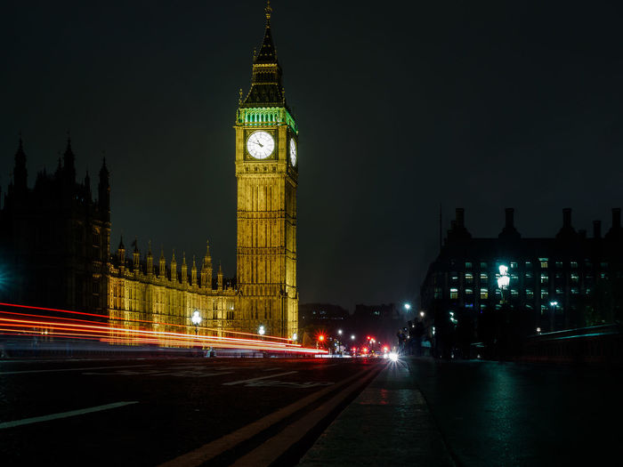 Light trails over road by illuminated big ben against sky at night in city