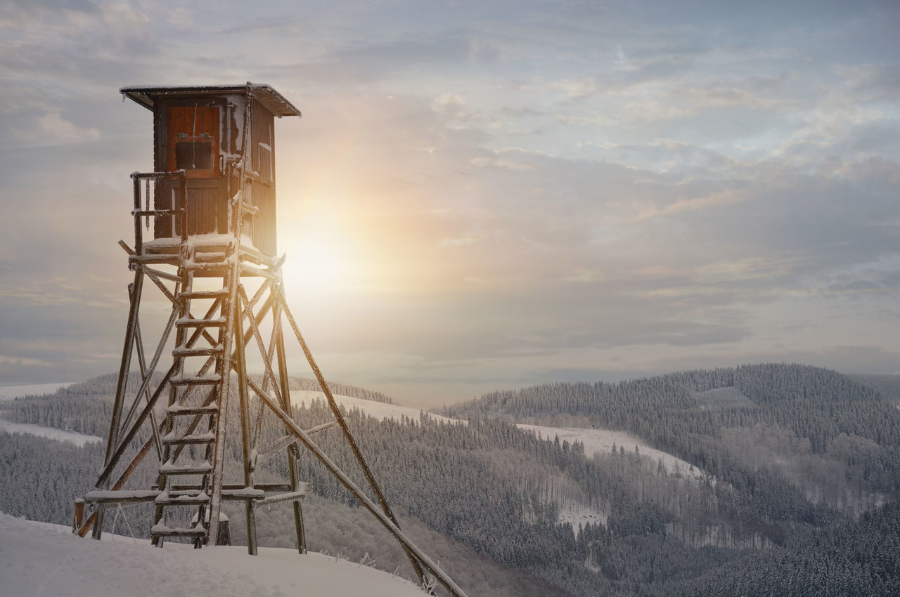 Lookout tower at snowcapped mountain against sky during sunrise
