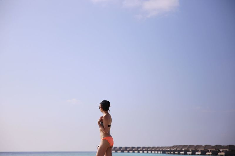 Side view of woman wearing bikini while walking at beach against sky during sunny day