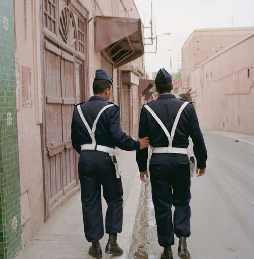 Rear view of men walking on street
