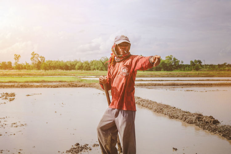 Farmer Pointing While Standing On Field Against Sky