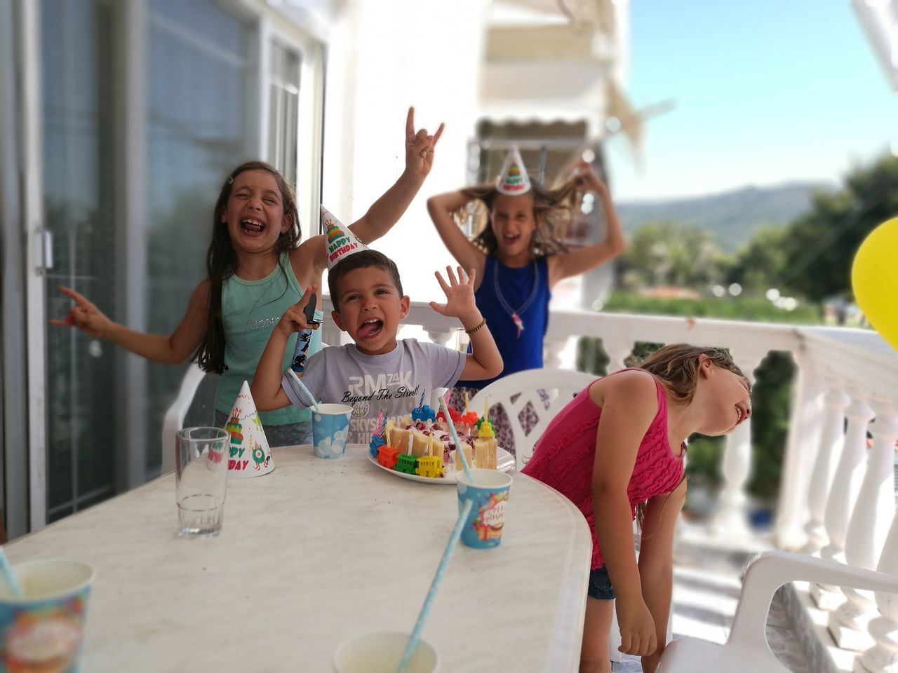 childhood, girls, real people, smiling, happiness, arms raised, mother, daughter, togetherness, enjoyment, father, looking at camera, lifestyles, casual clothing, love, celebration, fun, day, portrait, family, standing, cheerful, boys, leisure activity, bonding, child, outdoors, men, women, full length, architecture, young adult