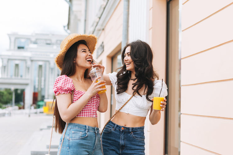 Happy young women friends in summer clothes with juice in hands having fun on summer city street