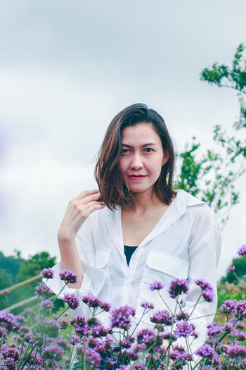 Portrait of a beautiful young woman standing by purple flowering plants against sky