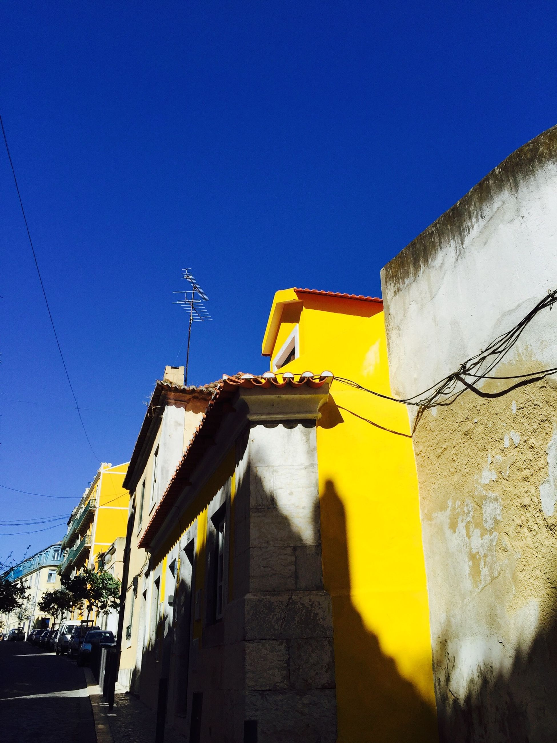 clear sky, architecture, building exterior, built structure, blue, low angle view, yellow, copy space, wall - building feature, sunlight, street, street light, outdoors, shadow, day, no people, building, sky, road, wall