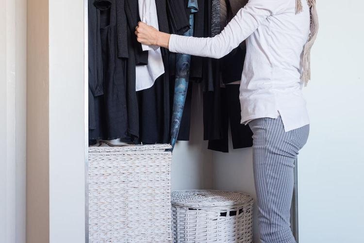 Woman standing at wardrobe choosing clothing Woman Adult Clothing Day Human Hand Indoors  Midsection People Standing Wardrobe