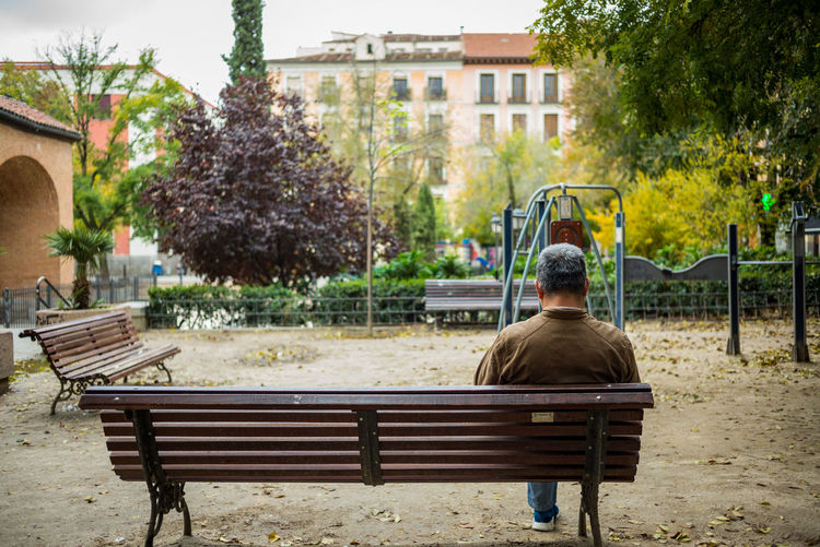 Rear view of man sitting on bench