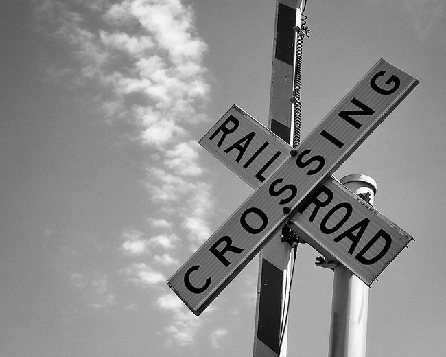 Railraod Crossing Sign Text Sky Sign Low Angle View Cloud - Sky No People Pole Day Guidance Information Capital Letter Road Sign Information Sign Symbol Outdoors Railroad Crossing Sign