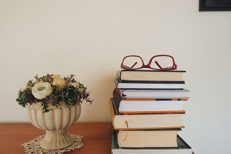 Close-up of books on table against wall at home