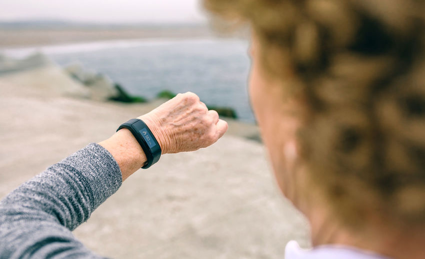 Unrecognizable senior woman looking her smart watch Checking Heartbeat Horizontal Lifestyle Pier Running Woman Activity Aged Bay Calories Cheerful Dock Elderly Healthy One Person Outdoors Real People Sea Senior Smart Watch Sports Clothing Training Unrecognizable Person Wristband