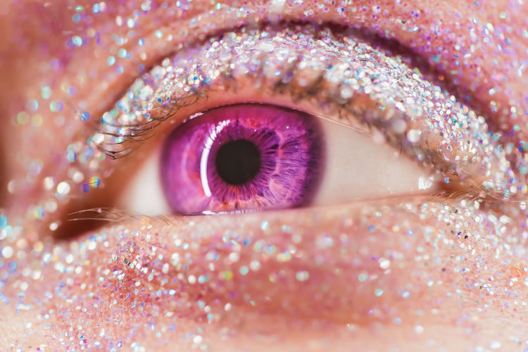 Macro violet or pink female eye with glitter eyeshadow, colorful sparks, crystals. Beauty background, fashion glamour makeup concept. Fantasy look. Holiday evening make-up detail. Eye Sensory Perception Human Body Part Human Eye Eyesight Close-up Body Part Extreme Close-up Eyelash One Person Adult Young Adult Women Blue Eyes Iris - Eye Make-up Macro Beautiful Woman Beauty Human Face Eyeball Purple