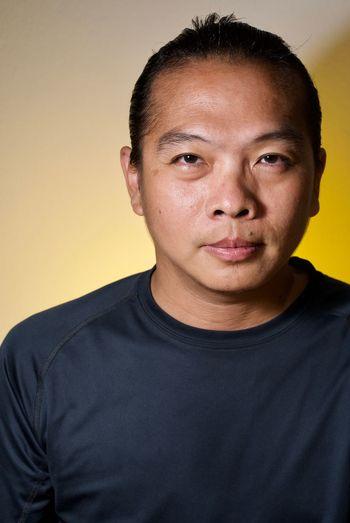 Close-up portrait of mature man against colored background