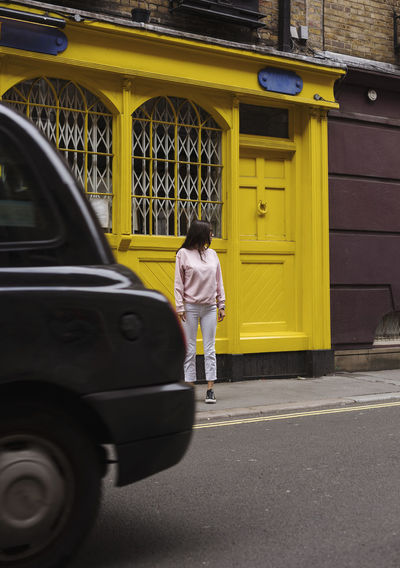 Rear view of woman standing against yellow door