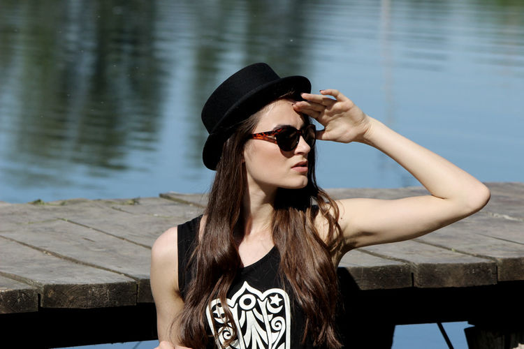 Young woman in sunglasses looking away while standing by lake